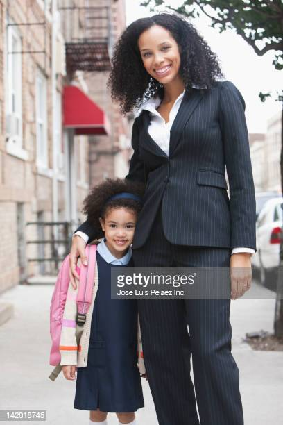 Mixed race mother and daughter hugging on sidewalk