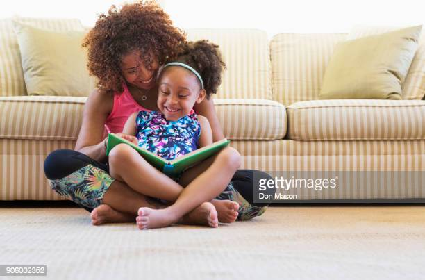mixed race mother and daughter reading book on floor near sofa - één ouder stockfoto's en -beelden