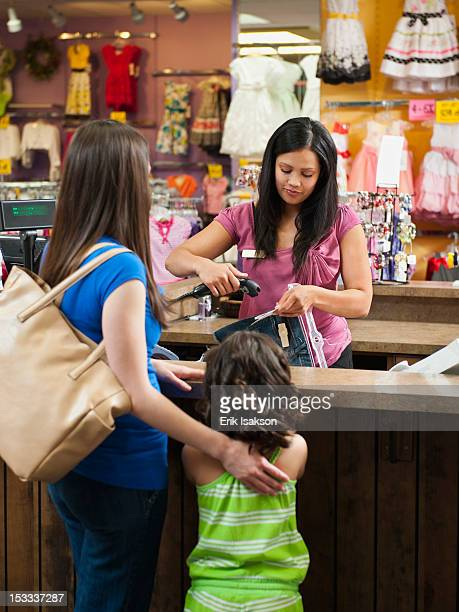 Mixed race mother and daughter shopping in children's clothing store