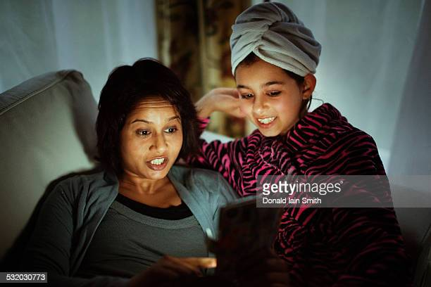 Mixed race mother and daughter using digital tablet at night