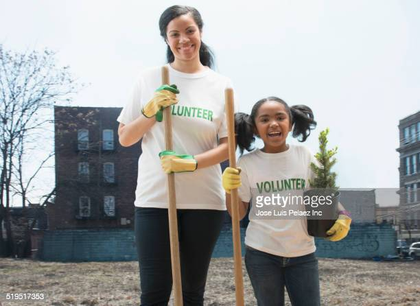 Mixed race mother and daughter volunteering together in urban park