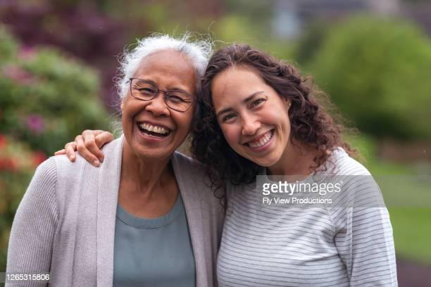 gemengd ras moeder en dochter lopen en praten samen buiten - volwassen nageslacht stockfoto's en -beelden