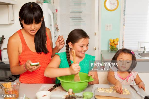 Mixed race mother and daughters baking in kitchen