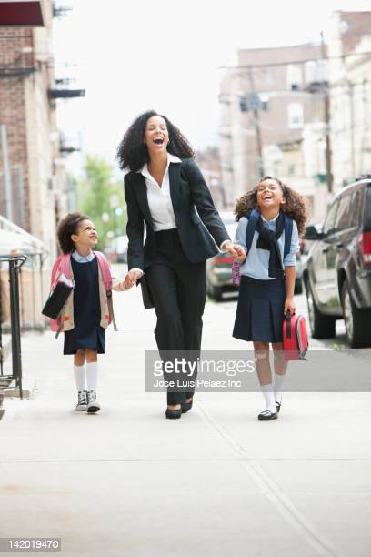 Mixed race mother and daughters walking on sidewalk