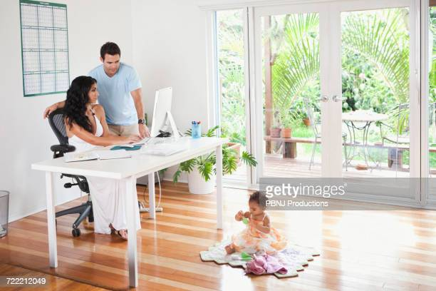 Mixed Race mother and father using computer and watching baby daughter
