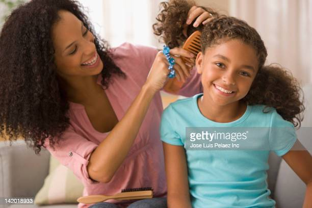 Mixed race mother brushing daughter's hair