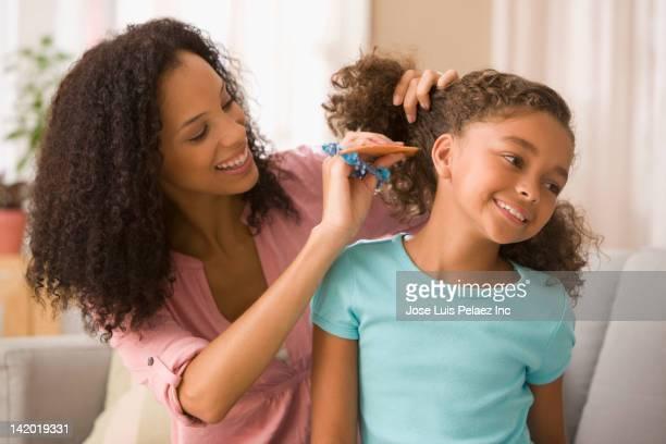 mixed race mother brushing daughter's hair - penteando - fotografias e filmes do acervo