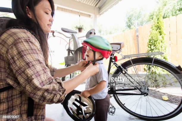 Mixed race mother buckling helmet on son