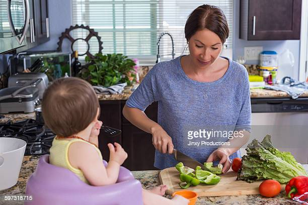 Mixed race mother chopping vegetables with daughter in kitchen