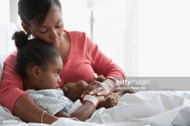 Mixed race mother comforting child in hospital bed