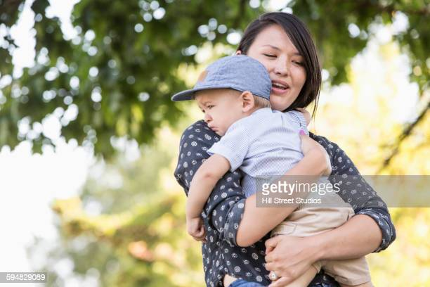 Mixed race mother comforting crying son outdoors