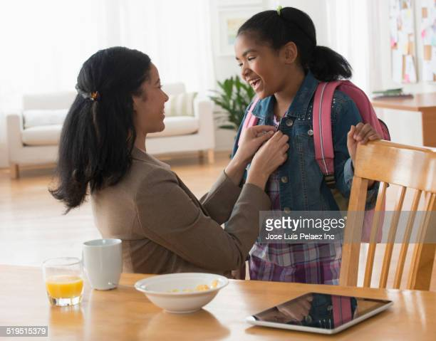 Mixed race mother fastening jacket of daughter at breakfast table