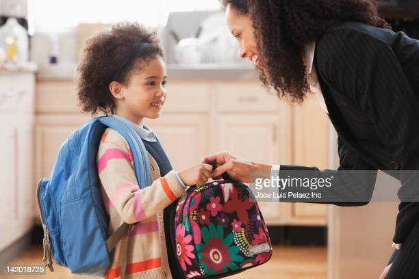 mixed race mother handing lunch box to daughter - voorbereiding stockfoto's en -beelden