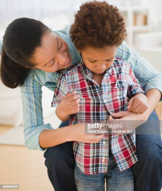 Mixed race mother helping son to dress
