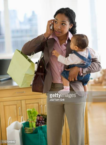 Mixed race mother holding baby and talking on cell phone