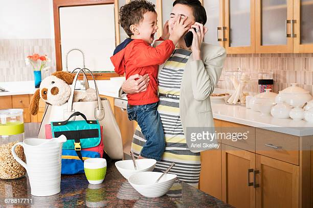 Mixed Race mother holding crying son while talking on cell phone