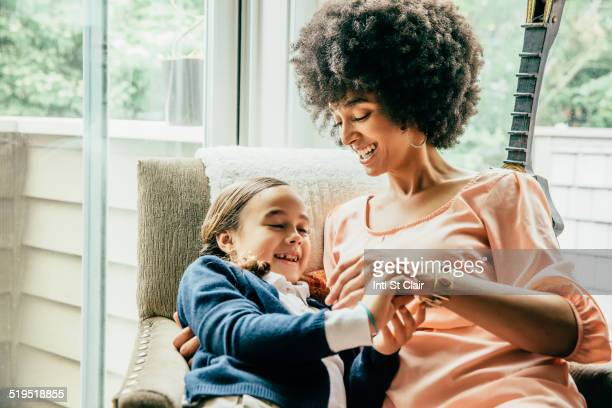 Mixed race mother holding daughter in armchair