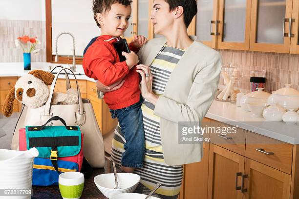 Mixed Race mother holding son in kitchen