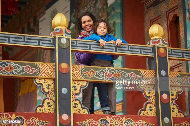 mixed race mother holding son on balcony - thimphu stock pictures, royalty-free photos & images