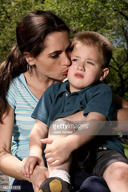 mixed race mother kissing hurt son in park - leg kissing stock photos and pictures
