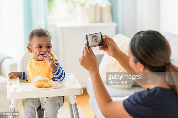 Mixed race mother photographing messy baby boy in high chair