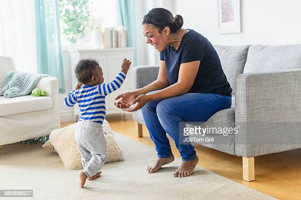 Mixed race mother playing with baby son in living room