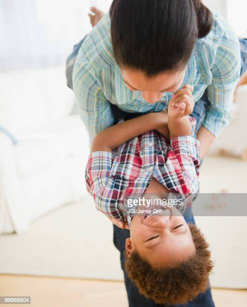 mixed race mother playing with son - mixed wrestling stock pictures, royalty-free photos & images