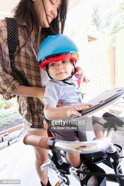 Mixed race mother riding bicycle with son