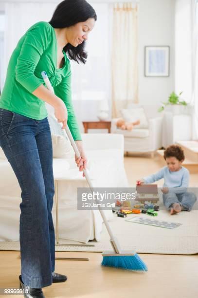 Mixed race mother sweeping floor