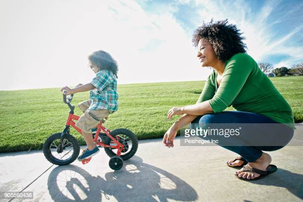 Mixed race mother watching son ride bicycle