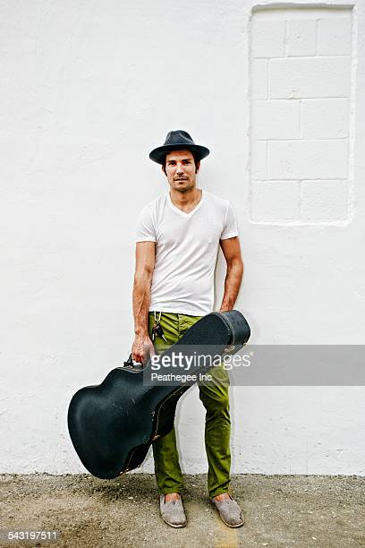 mixed race musician carrying guitar case - guitar case stock pictures, royalty-free photos & images