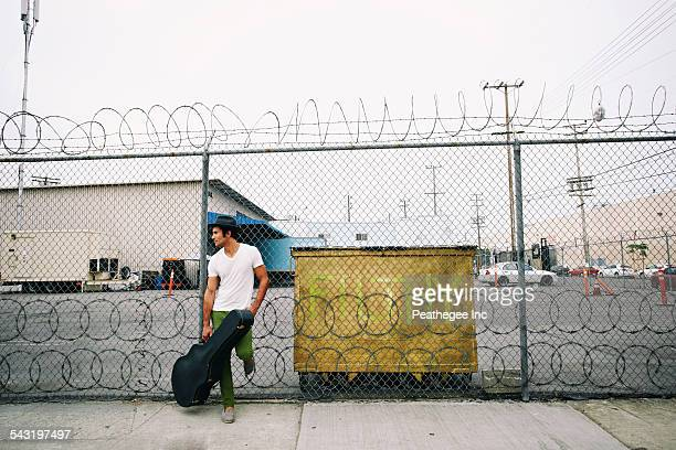 Mixed race musician leaning on fence holding guitar case