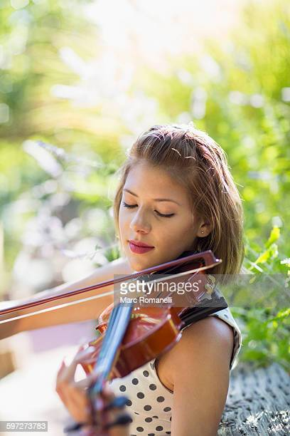 Mixed race musician playing violin outdoors