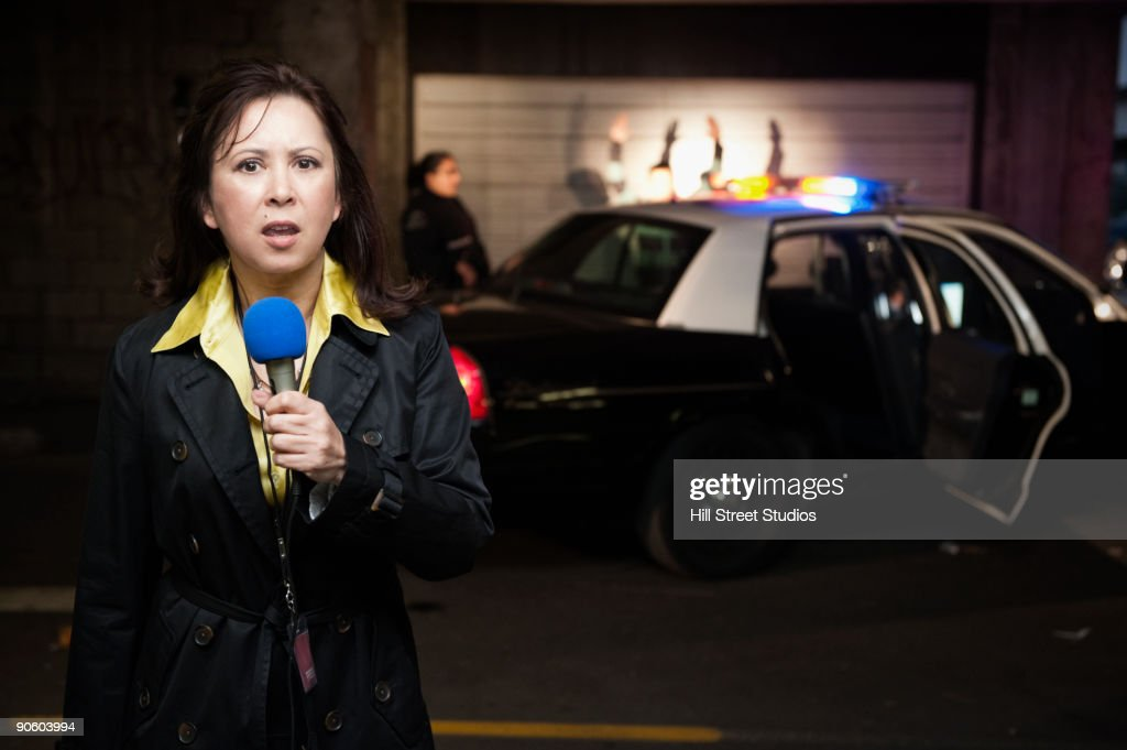 Mixed race news reporter reporting at crime scene : Stock Photo