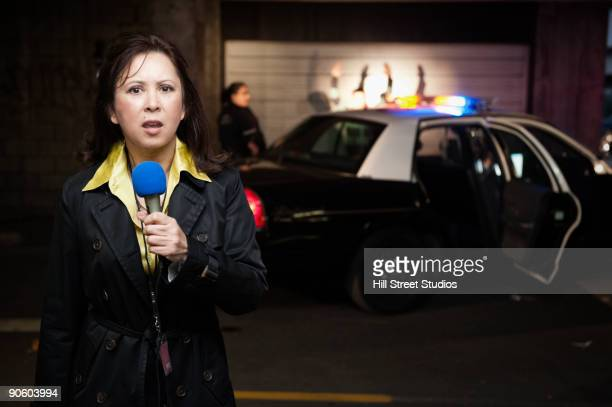 Mixed race news reporter reporting at crime scene