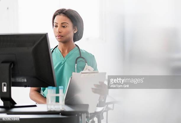 Mixed race nurse smiling at computer