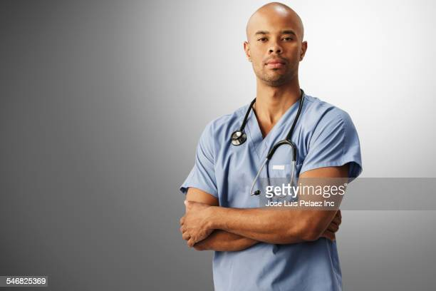 Mixed race nurse standing with arms crossed