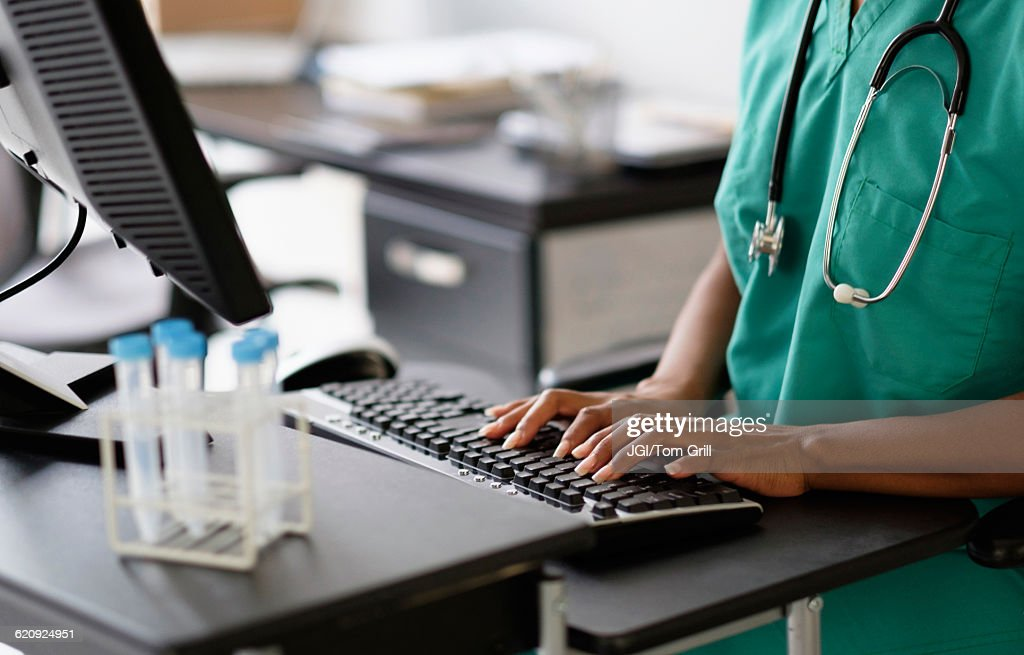 Mixed race nurse working at computer : Stock Photo