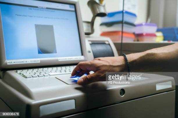 mixed race nurses using fingerprint scanner - biometrics stock photos and pictures