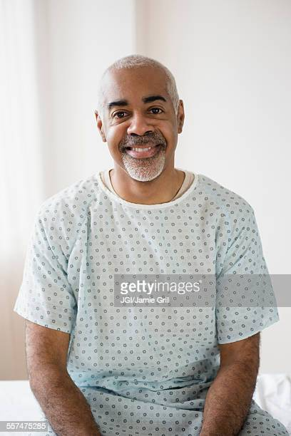 Mixed race older man sitting on hospital bed