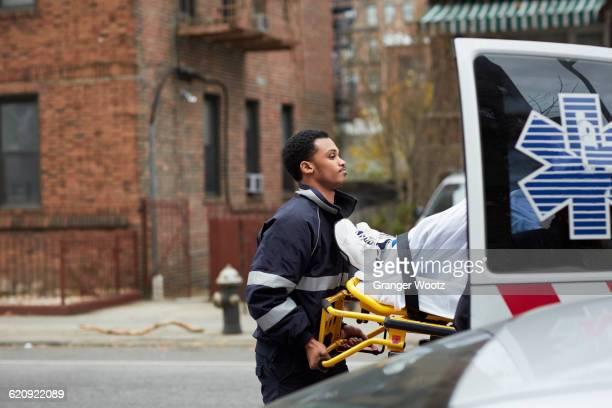 mixed race paramedic loading patient into ambulance - 救急救命士 ストックフォトと画像
