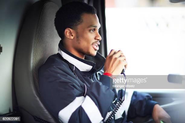 Mixed race paramedic using walkie-talkie