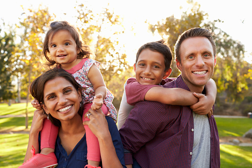 Mixed race parents carry their kids piggyback in a park 620382500