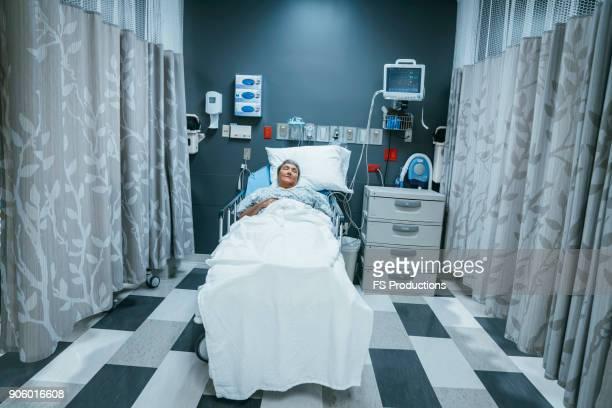 mixed race patient sleeping in hospital bed - chambre d'hôpital photos et images de collection