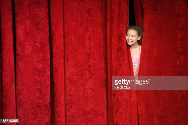 Mixed race person hiding behind stage curtain