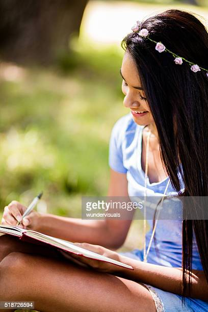 Mixed Race Person sitting at tree writing in journal