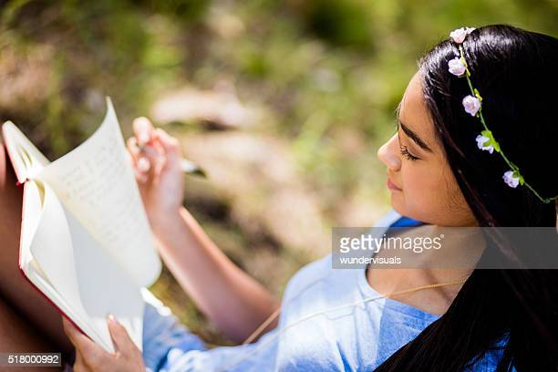 mixed race person sitting outside writing in journal - dagboek stockfoto's en -beelden