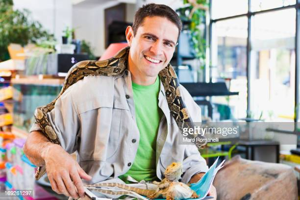 mixed race pet store owner with animals - reptile stock pictures, royalty-free photos & images