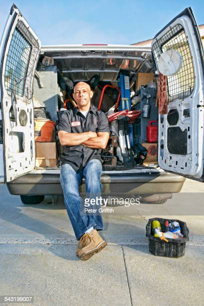 Mixed race plumber sitting in van