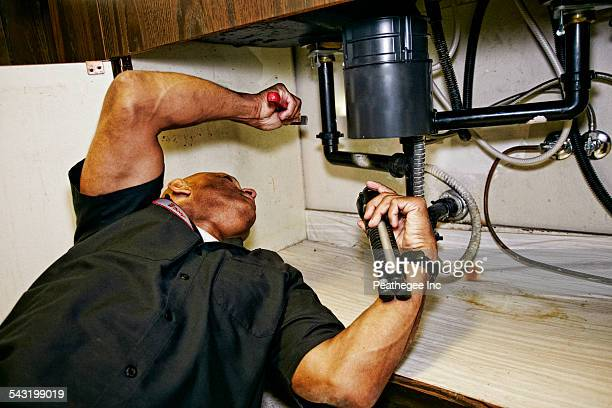 Mixed race plumber working under sink